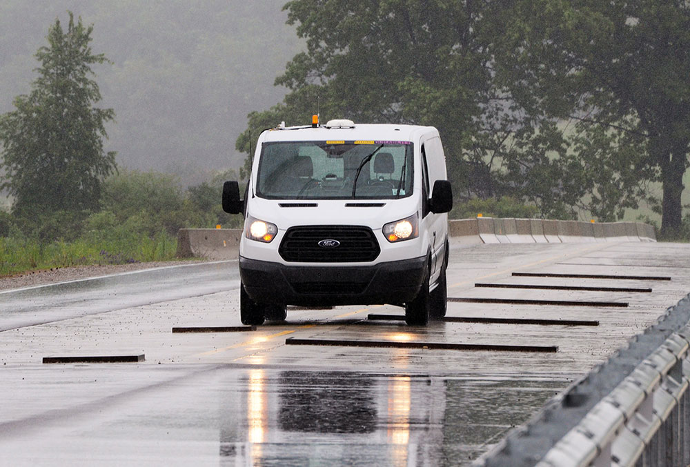 A 2014 Ford Transit Van drives on a proving ground in Michigan